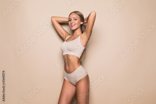 Obraz na plátně Young woman in underwear on beige background