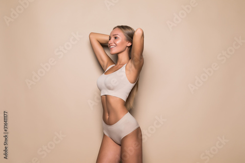 Young pretty woman standing in beige lingerie isolated on beige background