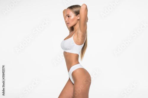 Obraz Young woman with beautiful slim perfect body in white bikini isolated white background - fototapety do salonu
