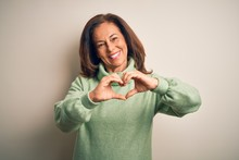 Middle Age Beautiful Woman Wearing Casual Turtleneck Sweater Over Isolated White Background Smiling In Love Doing Heart Symbol Shape With Hands. Romantic Concept.