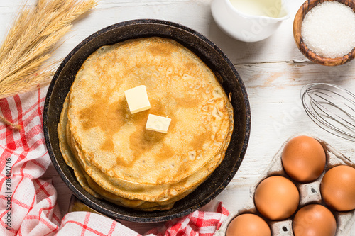 Fototapeta Crepes or thin pancakes in the frying pan with ingredients for cooking. obraz