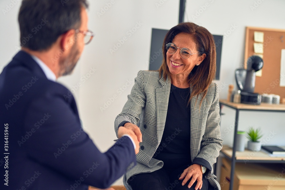 Fototapeta Two middle age business workers smiling happy and confident. Working together with smile on face shaking hands at the office