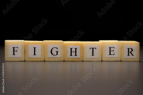 Photo The word FIGHTER written on wooden cubes isolated on a black background