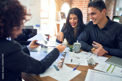 Fototapeta Young beautiful couple applying for mortgage. Sitting smiling happy meeting with real state agent considering mortgage loan at bank obraz