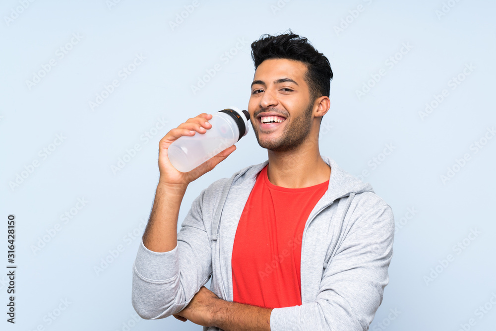 Fototapeta Sport man with a bottle of water over isolated blue wall