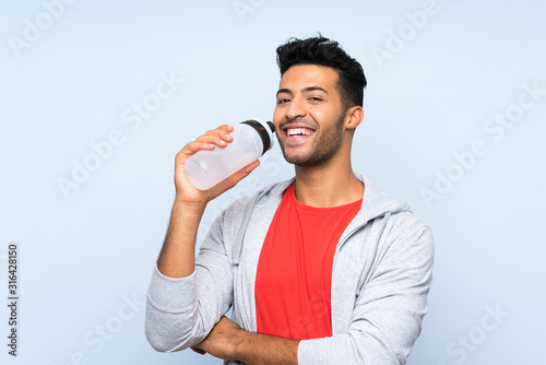 Fototapeta Sport man with a bottle of water over isolated blue wall obraz