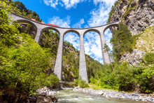 Landwasser Viaduct, Switzerland. Red Train Runs On High Railroad Bridge In Mountains. This Place Is Landmark Of Swiss Alps. Scenic View Of Famous Railway.