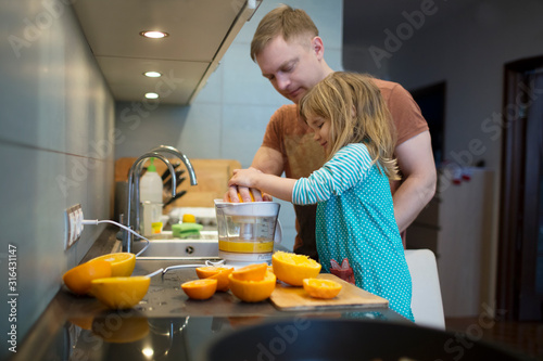 Father and child daughter cooking breakfast and squeeze out orange juice in the kitchen Canvas Print