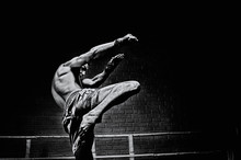 Thai Boxer In The Ring Hits With A Knee. The Concept Of Sports, Gyms, Boxing Clubs.