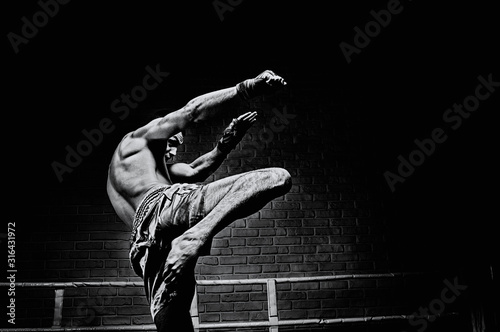 Canvas Print Thai boxer in the ring hits with a knee