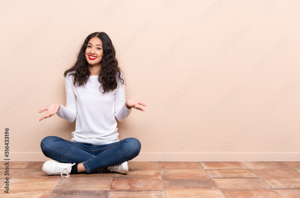 Fototapeta Young woman sitting on the floor smiling