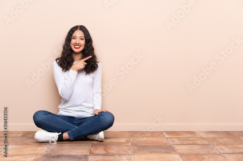Obraz Young woman sitting on the floor pointing to the side to present a product - fototapety do salonu