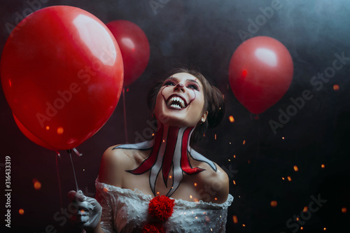 Leinwand Poster close-up portrait female clown woman scary crazy smiling laugh shows sharp teeth predator face, holding red balloons