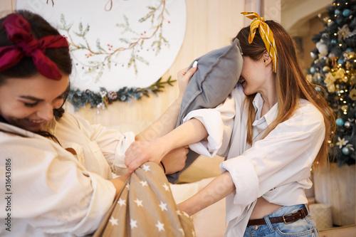 Obraz na płótnie Indoor image of stylish cute teenage girls fooling around having pillow fight in cozy bedroom