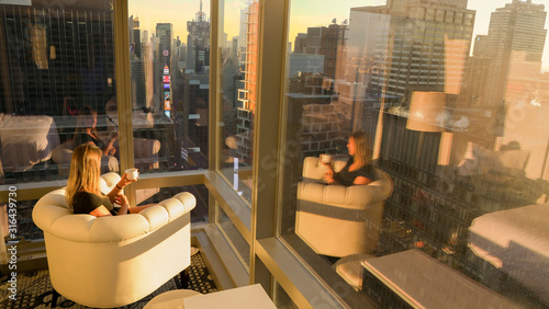 Fototapeta COPY SPACE: Young woman sitting in armchair while observing New York at sunrise. obraz