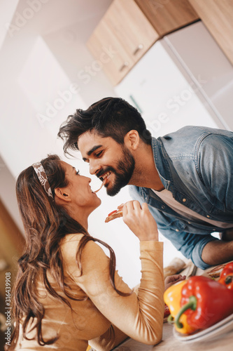 Photo A goofy couple sharing a slice of ham with their mouth in the kitchen - angled frame