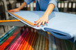 canvas print picture - Woman measures the fabric in textile store