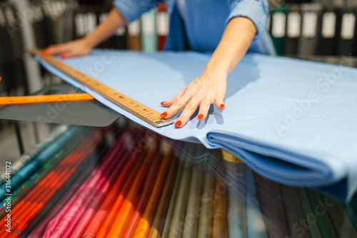 Obraz na płótnie Woman measures the fabric in textile store