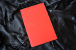Red book on black background. Relaxation mood, cultural activity. Freedom, information, knowledge concept. Empty book cover for advertisement image montage.