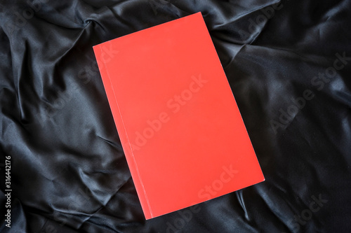 Obraz Red book on black background. Relaxation mood, cultural activity. Freedom, information, knowledge concept. Empty book cover for advertisement image montage.         - fototapety do salonu