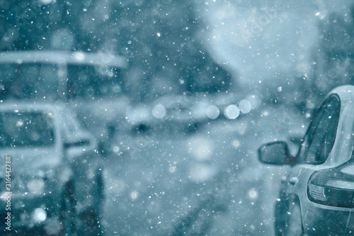 Fototapeta view of the winter road from the car, traffic in the seasonal city, bad weather in the northern city obraz