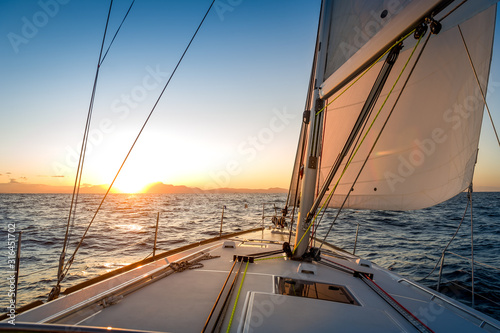 Chasing the sun at sailing yacht. Deck and sails of sailoat pointing to the sunrise. Mediterranean sea, Italy.