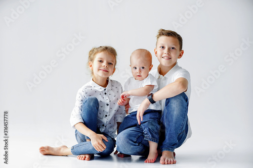 Happy sisters and brother are sitting on the floor on a white background Wallpaper Mural