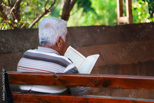 An unidentified muslim old religious man reads Quran concept Canvas Print