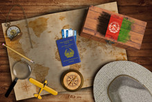 Top View Of Traveling Gadgets, Vintage Map, Magnify Glass, Hat And Airplane Model On The Wood Table Background. On Center, Official Passport Of Afghanistan And Your Flag.