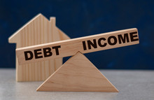 Debt And Income Balance On Wooden Scales On A Dark Background