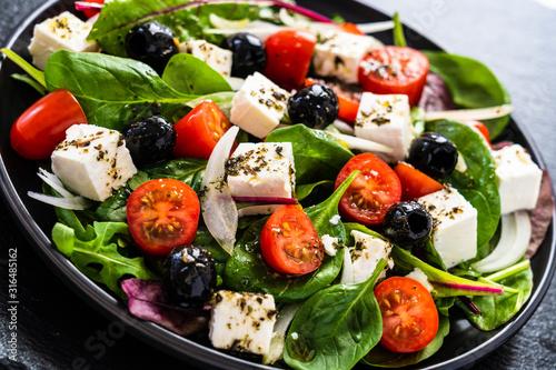 Fototapeta Fresh greek salad - feta cheese, tomato, lettuce, black olives and onion obraz