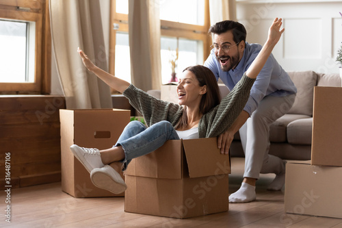 Obraz Happy couple have fun on moving day to new home - fototapety do salonu