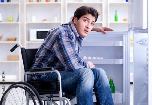Fotomural  Young disabled injured man opening the fridge door