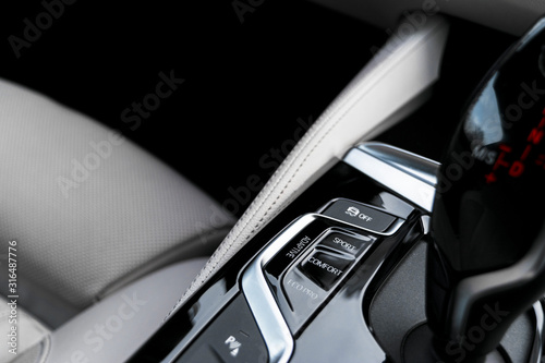 Cuadros en Lienzo  Track control buttons near automatic gear stick in a white leather interior of a modern car
