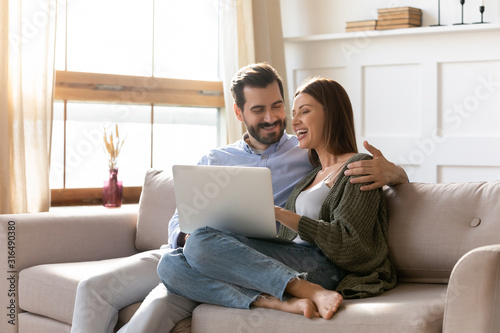 Young couple rest on sofa browsing internet on modern laptop