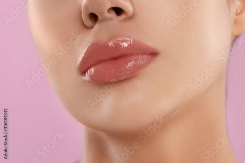 Young woman with beautiful full lips on pink background, closeup Wallpaper Mural