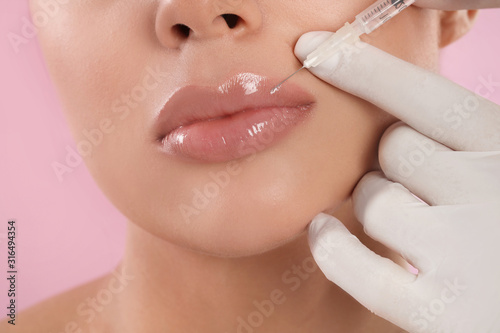 Fotografia Young woman getting lips injection on pink background, closeup