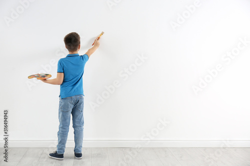 Fotomural  Little child painting on white wall indoors. Space for text