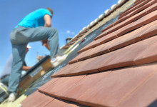 New Red Tiles On A Roof And Worker Standing Background Against The Blue Sky