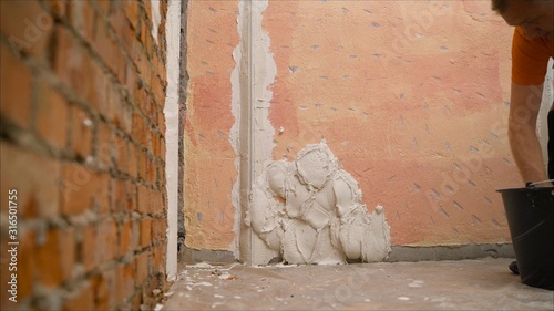 construction notched trowel and worker hands with white mortar on wall Canvas Print