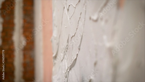 construction notched trowel and worker hands with white mortar on wall Wallpaper Mural