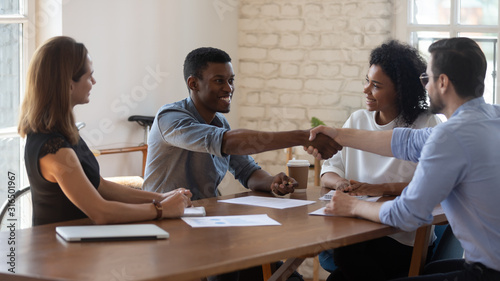 Happy diverse business partners shaking hands after successful negotiation