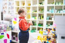 Happy Little Boy Chooses A Toys