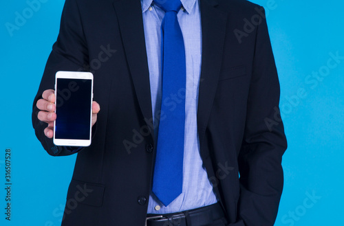 Fototapety, obrazy: businessman with mobile phone on blue background