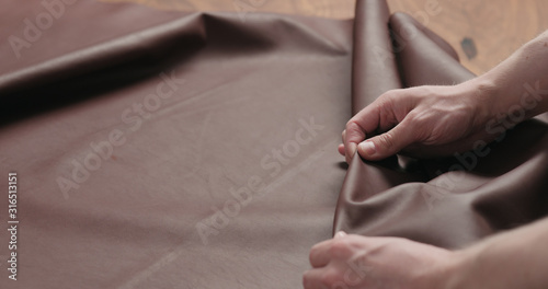 Fototapety, obrazy: man hand checking brown leather piece closeup