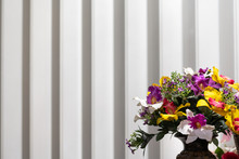 Bouquet Of Artificial Flowers On A Plastic Curtain Backdrop.
