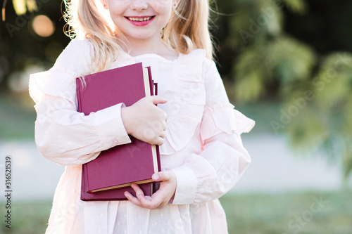 Smiling kid girl pupil 5-6 year old holding stack of books over green nature background closeup Canvas Print