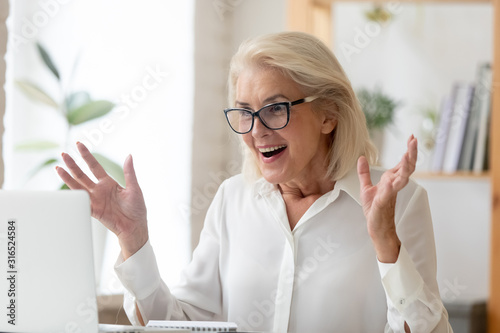 Middle-aged businesswoman feeling amazement received unbelievable online news Canvas Print