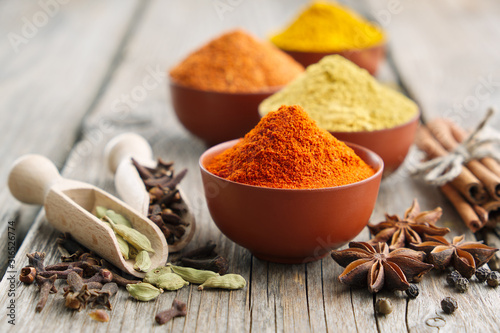 Fototapeta Aromatic spices and herbs: red pepper, turmeric, cardamom, cinnamon, cloves, anise, paprika. Ingredients for cooking. Ayurveda treatments obraz