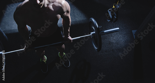 Fotografia Muscular strong athletic man with naked torso pumping up muscles in the gym, bod
